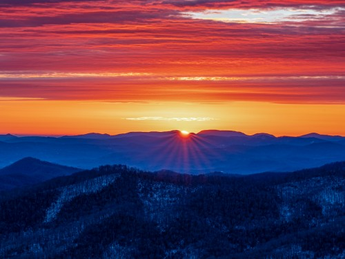 An extremely vibrant sunrise over snow-covered blue ridge mountains by Asheville Photography James Reynolds